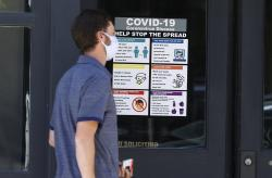 A pedestrian wears a face mask while passing by a sign placed on the door of a business in an effort to stop the rise of the new coronavirus Wednesday, May 20, 2020, in Denver