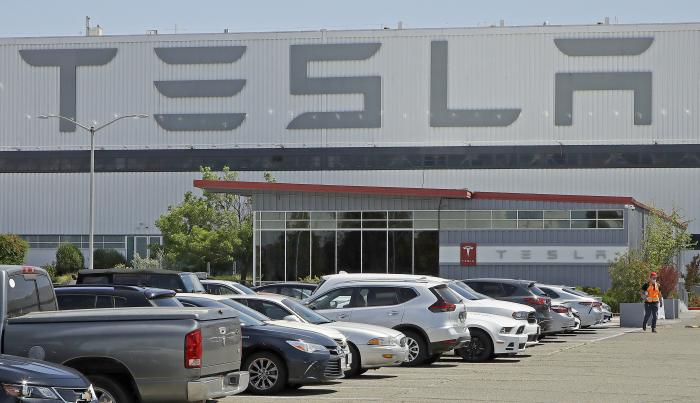 In this Monday, May 11, 2020 file photo, a man wearing a mask walks through the Tesla plant parking lot in Fremont, Calif.