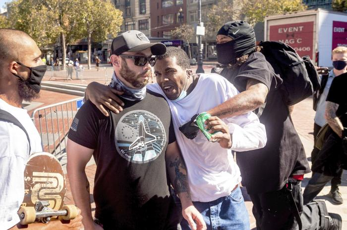 Philip Anderson, center, organizer of a free speech rally by conservative activists in San Francisco, is attacked by a counter-protester on Saturday, Oct. 17, 2020.