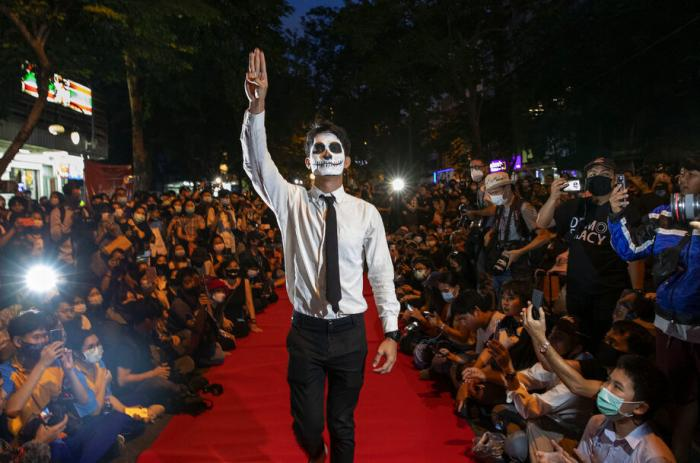 """Pro-democracy protesters perform on a mock """"red carpet"""" fashion show billed as a counterpoint to a fashion show being held by one of the monarchy's princesses nearby in Bangkok, Thailand."""