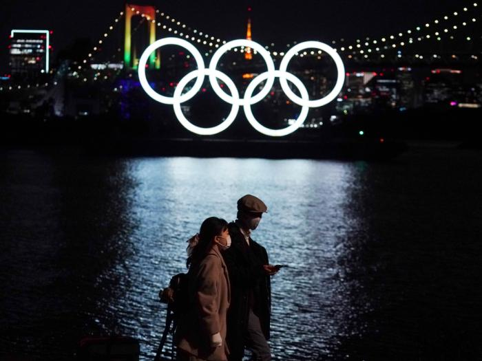 In this Dec. 1, 2020, file photo, a man and a woman walk past near the Olympic rings floating in the water in the Odaiba section in Tokyo