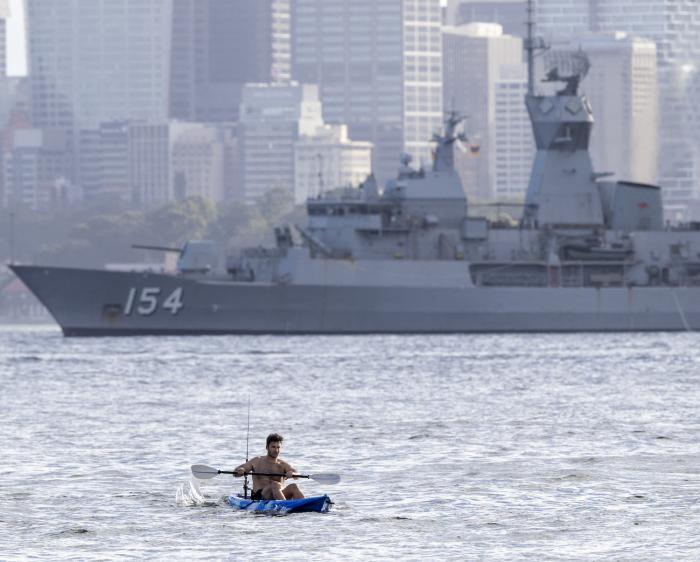 A man paddles his kayak past the HMAS Arunta, an Anzac-class frigate of the Royal Australian Navy, in Sydney harbor, Australia.