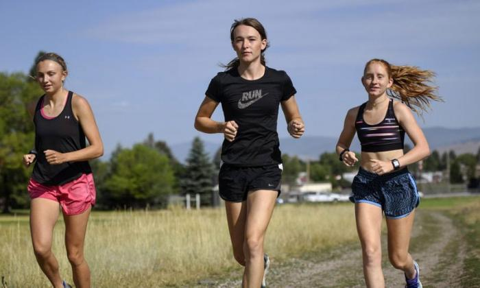 In this Aug. 15, 2019, file photo, is University of Montana cross country runner Juniper Eastwood, center, warming up with her teammates at Campbell Park in Missoula, Mont.