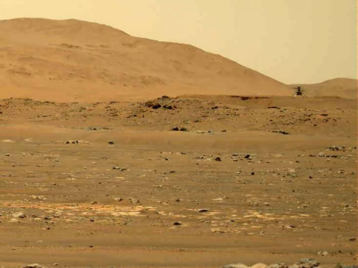 In this image taken by the Mars Perseverance rover and made available by NASA, the Mars Ingenuity helicopter, right, flies over the surface of the planet on Friday, April 30, 2021