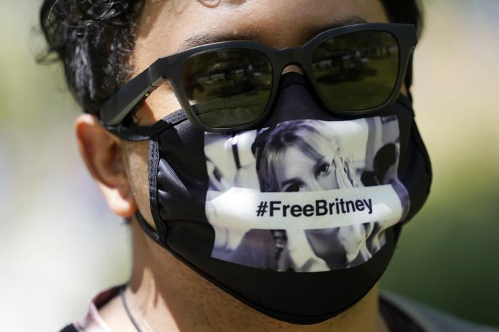 Britney Spears supporter Carlos Morales of Los Angeles wears a Free Britney mask outside a court hearing concerning the pop singer's conservatorship at the Stanley Mosk Courthouse.