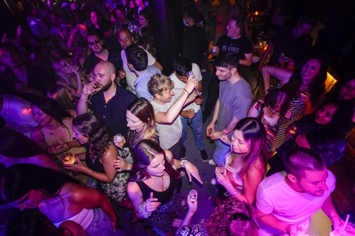 People drink on the dance floor shortly after the reopening, at The Piano Works in Farringdon, in London.
