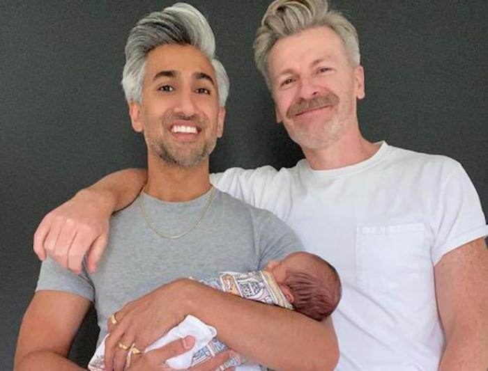 Tan France, left, holding his son Ismail France, with his husband Rob France, right.