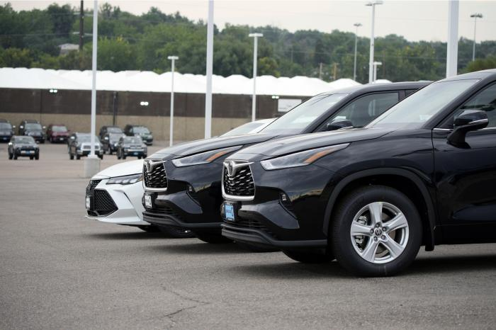 In this Sunday, Aug. 29, 2021, file photo, a pair of unsold 2021 Highlander sports utility vehicles and a Camry sedan are parked on the empty storage lot outside a Toyota dealership in Englewood, Colo.